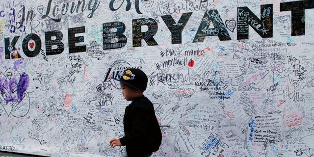 En pojke framför en minnesplats där den avlidne basketstjärnan Kobe Bryant.  Damian Dovarganes / TT NYHETSBYRÅN