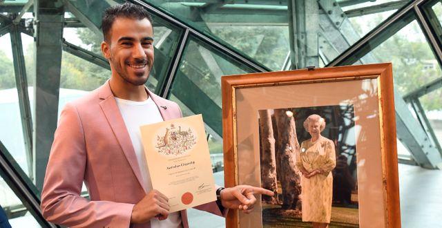 Hakeem al-Araibi och hans medborgarskapsintyg bredvid en bild av drottning Elizabeth.  WILLIAM WEST / AFP