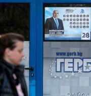 En kvinna passerar en reklamposter med Bojko Borisovs ansikte. Valentina Petrova / TT NYHETSBYRÅN