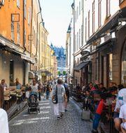 """Turister på uteserveringar intill Västerlånggatan i Gamla Stan en """"vanlig"""" sommar.  Pontus Lundahl/TT / TT NYHETSBYRÅN"""