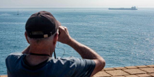 En man tittar på den iranska oljetankern Grace 1, som ligger för ankar utanför Gibraltar.  Marcos Moreno / TT NYHETSBYRÅN