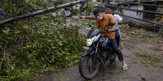Lokalbor passerar under en raserad elledning i Calcutta. Bikas Das / TT NYHETSBYRÅN