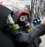 Människor med gasmask tar en selfie. Illustrationsbild. Efrem Lukatsky / TT NYHETSBYRÅN