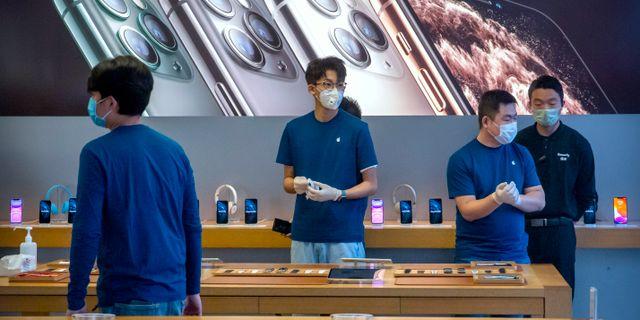 Anställda i ansiktsmasker i den återöppnade Applebutiken i Peking i fredags. Mark Schiefelbein / TT NYHETSBYRÅN