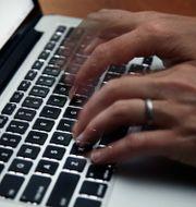 En person skriver på en dator.  Elise Amendola / TT NYHETSBYRÅN
