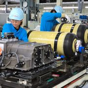Oct. 30, 2017, photo, workers of Toyota Motor Corp. set hydrogen-stored tanks, in yellow, to be placed into a Mirai fuel cell vehicle at the automaker's Motomachi plant, in Toyota, western Japan. Yuri Kageyama / TT NYHETSBYRÅN