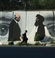 Väggmålning i Kabul av Washingtons fredsförhandlare Zalmay Khalilzad och talibanernas Mullah Abdul Ghani Baradar. Rahmat Gul / TT NYHETSBYRÅN