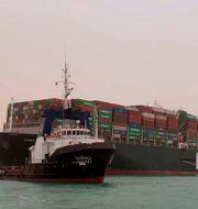 Bilder visar hur fartyget står på grund nästan tvärs öve Suezkanalen.  TT NYHETSBYRÅN/Suez Canal Authority via AP