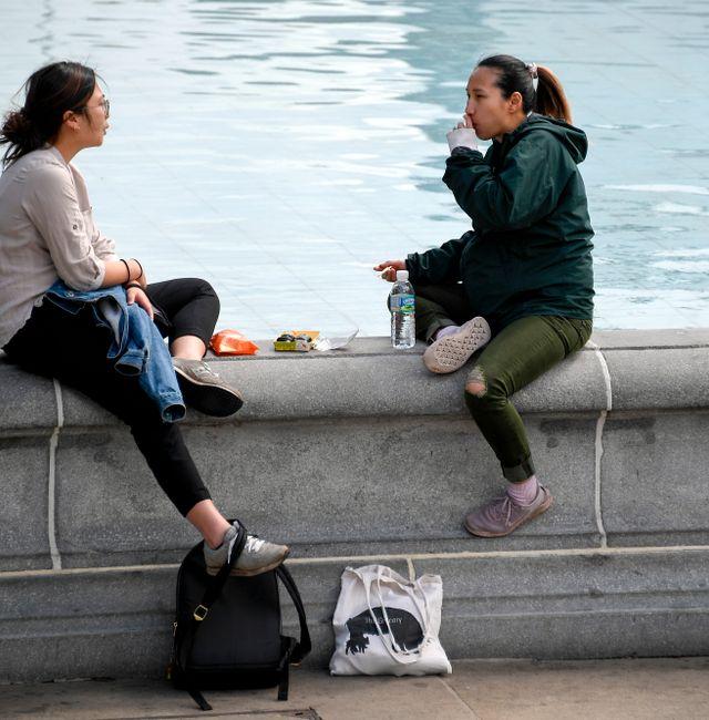 People eat on the edge of a fountain in Trafalgar Square, in London, Tuesday, May 18, 2021. Alberto Pezzali / TT NYHETSBYRÅN