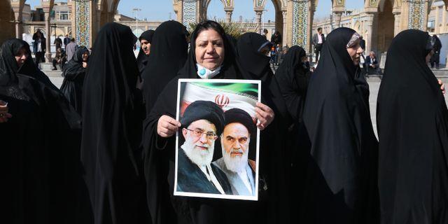 En iransk kvinna med ett porträtt på ayatollorna Khamenei och Khomeini. ATTA KENARE / TT NYHETSBYRÅN