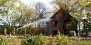 Brandkåren försöker förhindra att elden sprider sig till närliggande byggnader. Thomas Johansson/TT / TT NYHETSBYRÅN