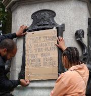 Demonstranter rev ner statyn av den kände slavhandlaren Edward Colston.  Kirsty Wigglesworth / TT NYHETSBYRÅN