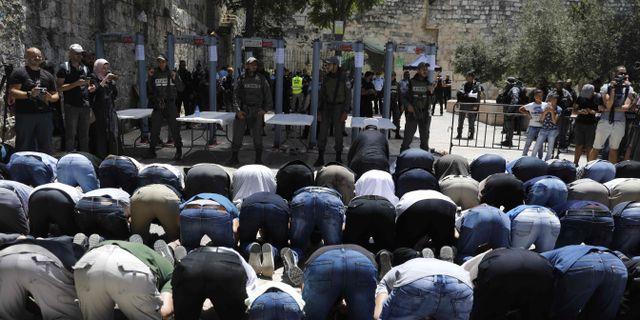 Muslimer ber utanför ingången till Tempelberget, som försetts med metalldetektorer.  MENAHEM KAHANA / AFP