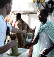 En av dem som räddats ombord på MV Aquarius får mat av en av besättningsmedlemmarna, på en bild från tisdagen som distribueras av  SOS Mediterranee. HANDOUT / TT NYHETSBYRÅN