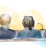 En av de åtalade med sina advokater. PETRA FRID/TT / TT NYHETSBYRÅN