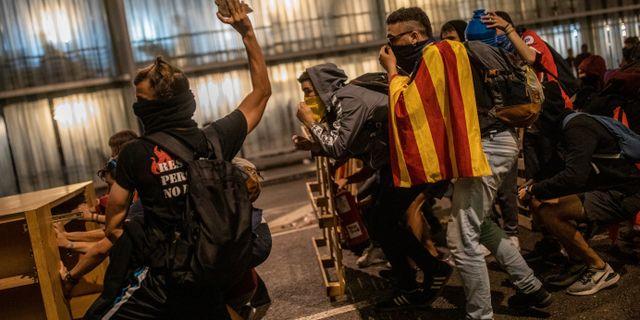 En demonstrant kastar sten mot polisen.  Bernat Armangue / TT NYHETSBYRÅN