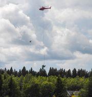 En helikopter bärgar vrakdelar efter olyckan. Patrick Trägårdh/TT / TT NYHETSBYRÅN