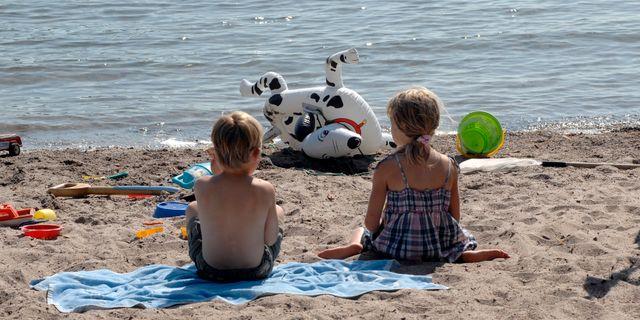 Två barn sitter på en sandstrand. Arkivbild från 2009.  Hasse Holmberg / TT / TT NYHETSBYRÅN