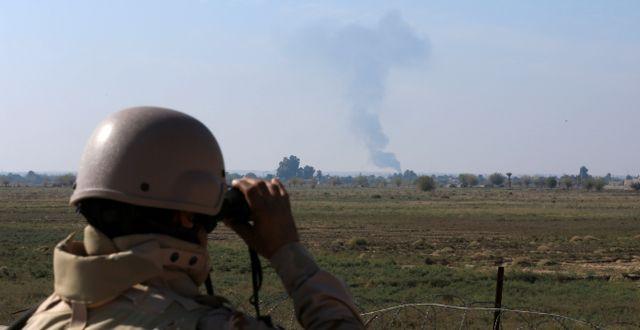En irakisk soldat tittar på rök efter ett luftangrepp mot IS. Hadi Mizban / TT NYHETSBYRÅN