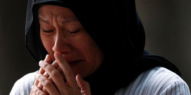 En kvinna gråter vid en minnesplats för offren. EDGAR SU / TT NYHETSBYRÅN