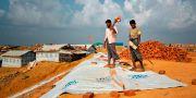 Flyktingar lägger plast på marken för att försöka förhindra jordskred. A. M. Ahad / TT / NTB Scanpix