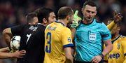 Michael Oliver (höger) blir omringad av Juventusspelare efter att ha dömt straff för Real Madrid. OSCAR DEL POZO / AFP