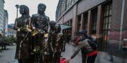 Människor lägger blommor vid en staty rest till minnet av evakueringen i närheten av Friedrichstrasses tågstation i centrala Berlin på måndagen.  Markus Schreiber / TT NYHETSBYRÅN