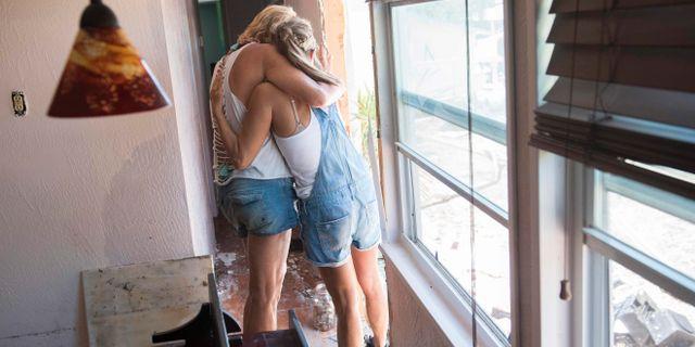 Patty Purdo kramar om en vän vars trailer-hem förstörts av stormen. SAUL LOEB / AFP