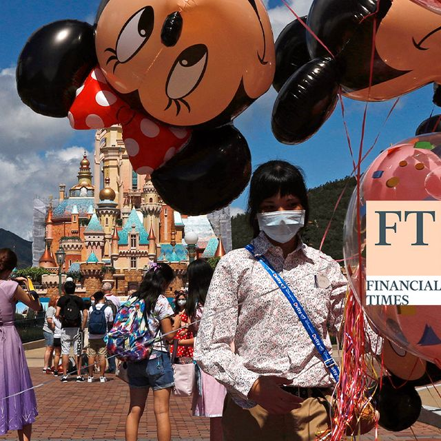 An employee wearing a face mask to prevent the spread of the new coronavirus, sells balloons at the Hong Kong Disneyland. Kin Cheung/AP