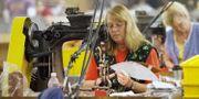 Kvinna syr amerikanska fotbollar på fabrik i USA. Illustrationsbild. Amy Sancetta / TT NYHETSBYRÅN