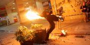 Demonstrant kastar brandbomber under protest. SUSANA VERA / TT NYHETSBYRÅN