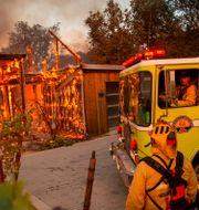 Brandmän arbetar med att släcka ett hus som börjat brinna på grund av skogsbränderna. JOSH EDELSON / AFP