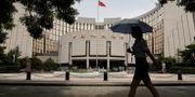 Arkivbild: En kvinna passerar framför Kinas Folkbanks huvudkontor i Peking. Jason Lee / TT NYHETSBYRÅN