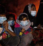 Flyktingarna värmer sig vid en brasa på stranden efter att de anlänt till Indonesien.  Zik Maulana / TT NYHETSBYRÅN