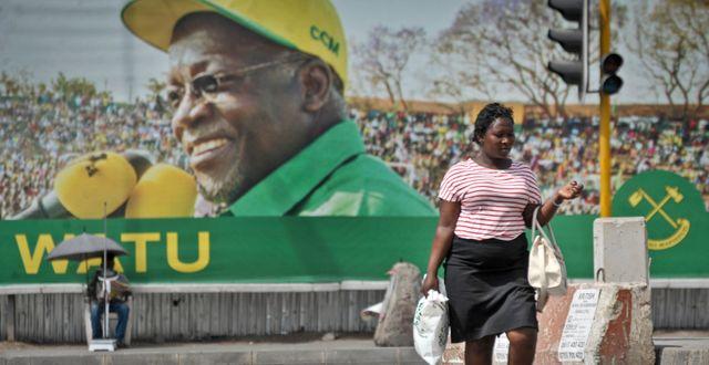 En kvinna i Dar es Salaam i Tanzania vandrar förbi en stor skylt med Tanzanias president John Magufulis ansikte. Khalfan Said / TT NYHETSBYRÅN