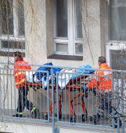 Patient som insjuknat i covid-19 bärs ut på bår. Petr David Josek / TT NYHETSBYRÅN