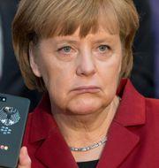 """Arkivbild: Angela Merkel med en """"avlyssningssäker"""" Blackberrytelefon vid Cebitmässan 2013. Julian Stratenschulte / TT NYHETSBYRÅN"""