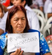 """Kvinna i Brasilien protesterar mot Vale efter katastrofen. På papperet står det """"Vale, mördare"""". Gustavo Andrade / TT NYHETSBYRÅN"""