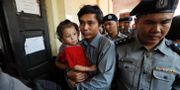 Kyaw Soe Oo bär sin dotter Moe Thin Wai Zin när han eskorteras i handklovar. JORGE SILVA / TT NYHETSBYRÅN