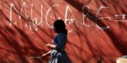 Kvinna går förbi en vägg där någon klottrat Mugabes namn.  Tsvangirayi Mukwazhi / TT NYHETSBYRÅN