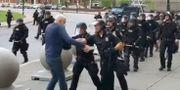 Poliserna knuffar mannen till marken.  Mike Desmond / TT NYHETSBYRÅN