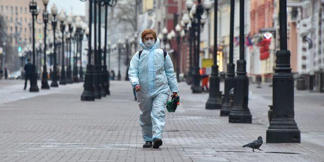 En kvinna i skyddskläder i ett tomt Moskva. VASILY MAXIMOV / TT NYHETSBYRÅN