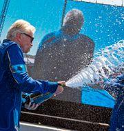 Richard Branson sprutar champagne på Beth Moses efter flighten.  Andres Leighton / TT NYHETSBYRÅN