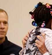 Donald Trump kramar om ett barn som drabbats av ovädret Harvey. KEVIN LAMARQUE / TT NYHETSBYRÅN