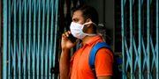 Man i ansiktsmask pratar i mobil i Indien.  Bikas Das / TT NYHETSBYRÅN