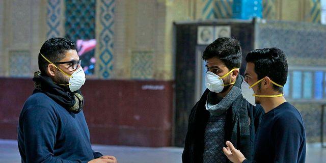 Människor i munskydd i Iran.  Anmar Khalil / TT NYHETSBYRÅN