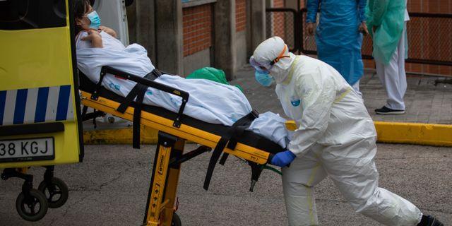 Sjukvårdare lyfter bår med patient i Spanien.  Bernat Armangue / TT NYHETSBYRÅN
