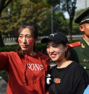 Två kvinnor tar selfies i samband med militärparaden i Peking under 70-årsfirandet av Folkrepubliken Kina. HECTOR RETAMAL / AFP