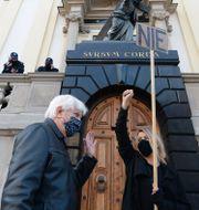 """En kvinnlig demonstrant håller ett plakat med texten """"nej"""" framför en kyrka i Warszawa. Czarek Sokolowski / TT NYHETSBYRÅN"""