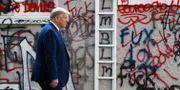 Donald Trump vandrar förbi en vandaliserad husfasad på sin promenad från Vita huset mot kyrkan St John igår.  Patrick Semansky / TT NYHETSBYRÅN